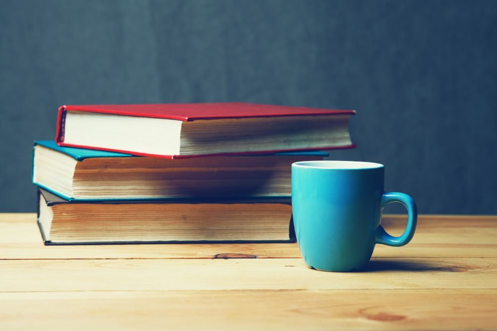 stack of books next to coffee cup